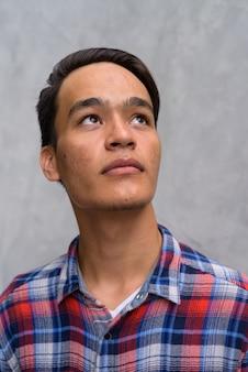 Junger hübscher indischer mann gegen betonmauer in den straßen