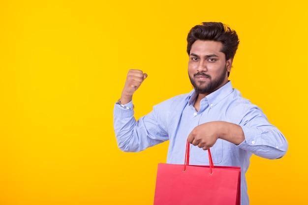 Junger hübscher indischer mann mit einem bart hält rote einkaufstaschen, die auf einer gelben wand aufwerfen