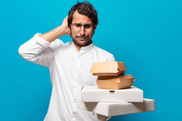 Junger hübscher indischer mann nehmen fast-food-konzept weg