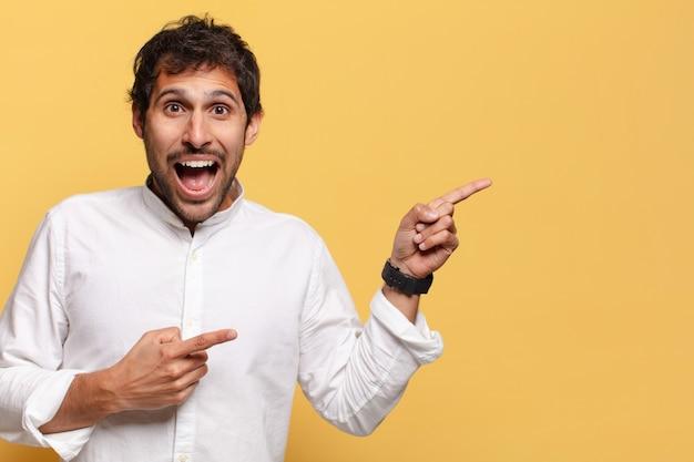 Junger hübscher indischer mann. schockierter oder überraschter ausdruck