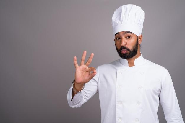 Junger hübscher indischer mannkoch, der ok zeichen macht