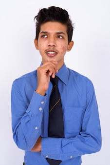 Junger hübscher indischer teenager als geschäftsmann auf weiß