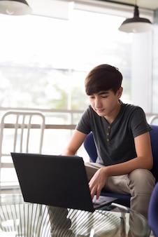 Junger hübscher iranischer teenager, der zu hause entspannt