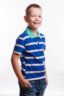 Junger hübscher junge, der am studio als mode-modell aufwirft.
