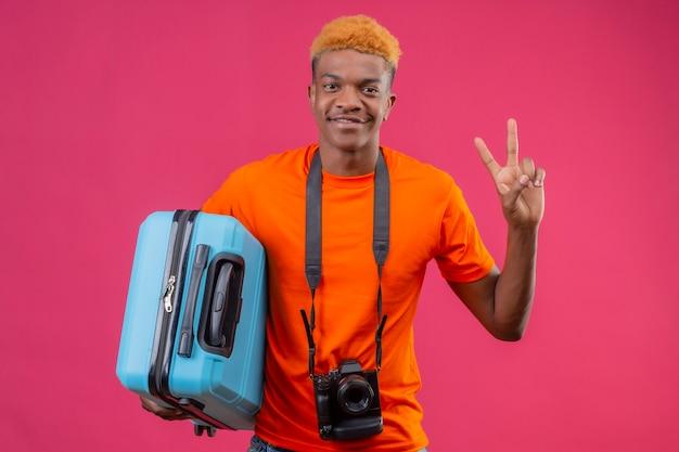 Junger hübscher junge, der orange t-shirt hält, der reisekoffer hält, der freundlich siegreiches zeichen zeigt
