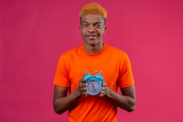 Junger hübscher junge, der orange t-shirt hält wecker hält, der mit glücklichem gesicht über rosa wand steht