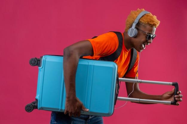 Junger hübscher junge, der orange t-shirt mit kopfhörern auf kopf hält, der reisekoffer hält