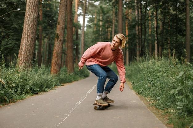 Junger hübscher junger mann mit einer frisur in einem rosa pullover läuft auf einem skateboard im park