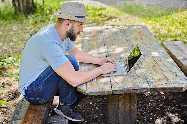 Junger hübscher kaukasischer bärtiger mann mit hut auf seinem kopf sitzt auf holztisch im wald und arbeitet mit computer.