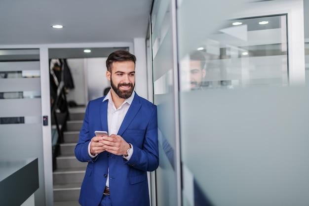 Junger hübscher kaukasischer geschäftsmann im anzug, der in der halle der maklerfirma steht und smartphone verwendet.