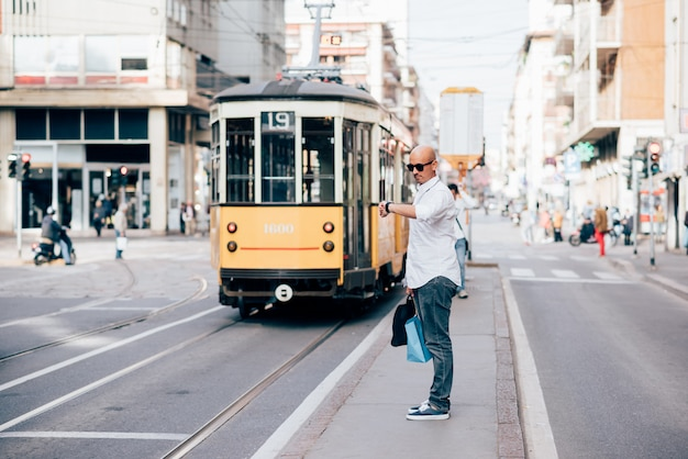Junger hübscher kaukasischer kahler geschäftsmann, der auf die tram wartet