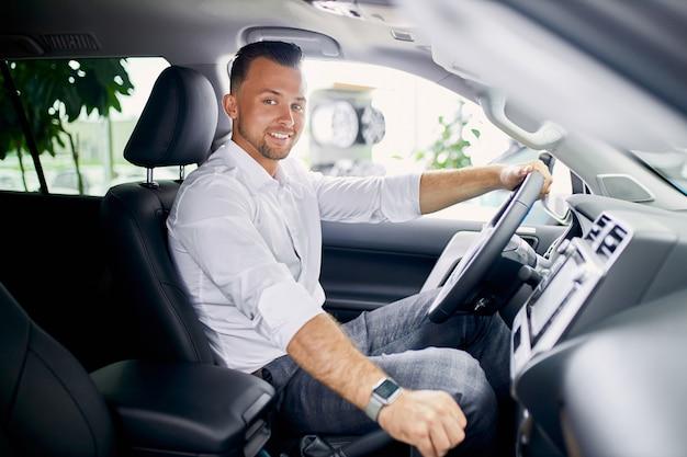 Junger hübscher kaukasischer kerl sitzt hinter dem lenkrad des neuen automobils