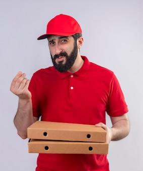Junger hübscher kaukasischer lieferbote, der rote uniform und kappe hält, die pizzaschachteln hält und geld gestikuliert, das kamera lokalisiert auf weißem hintergrund betrachtet