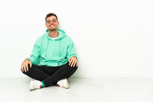 Junger hübscher kaukasischer mann, der auf dem boden mit gläsern und glücklich sitzt