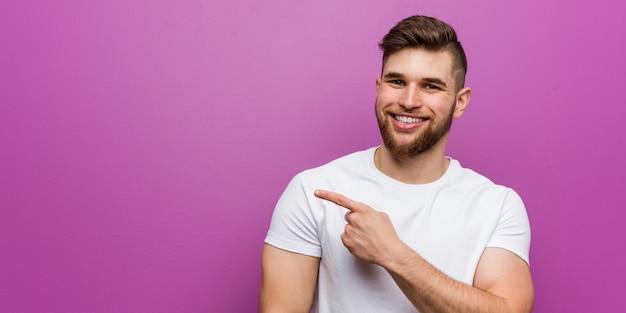 Junger hübscher kaukasischer mann, der beiseite lächelt und zeigt und etwas auf leerstelle zeigt.