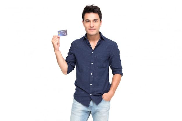 Junger hübscher kaukasischer mann, der, darstellend lächelt und stellen kreditkarte für die zahlung dar