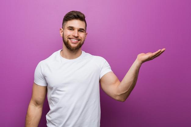 Junger hübscher kaukasischer mann, der einen kopienraum auf einer palme zeigt und eine andere hand auf taille hält.