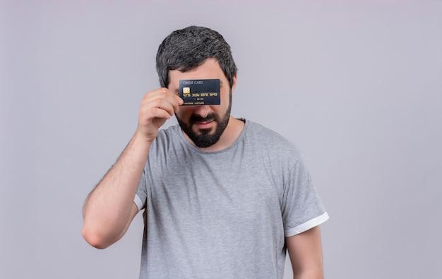 Junger hübscher kaukasischer mann, der hinter kreditkarte lokalisiert und versteckt auf weißem hintergrund mit kopienraum hält