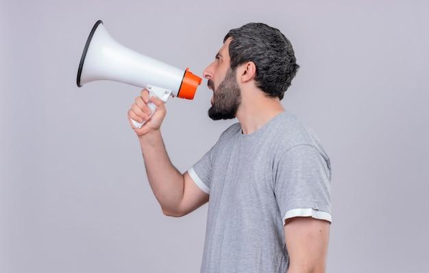 Junger hübscher kaukasischer mann, der in der profilansicht steht und im lautsprecher lokalisiert auf weißem hintergrund mit kopienraum schreit