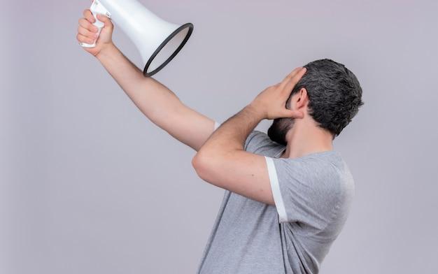 Junger hübscher kaukasischer mann, der in der profilansicht steht und lautsprecher aufstellt, der hand auf gesicht setzt und seinen kopf zur seite isoliert auf weißem hintergrund dreht