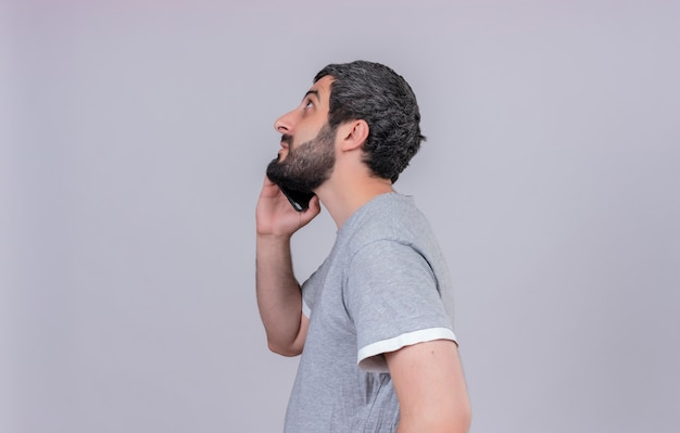 Junger hübscher kaukasischer mann, der in der profilansicht steht und oben am telefon lokalisiert auf weißem hintergrund mit kopienraum steht
