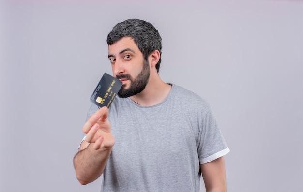 Junger hübscher kaukasischer mann, der kreditkarte in richtung kamera ausdehnt und es lokalisiert auf weißem hintergrund mit kopienraum betrachtet