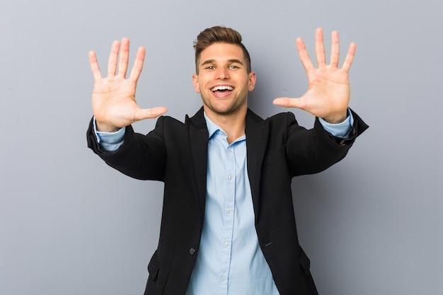 Junger hübscher kaukasischer mann, der nummer zehn mit händen zeigt.