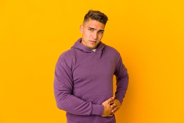 Junger hübscher kaukasischer mann isoliert mit einem leberschmerz, bauchschmerzen.