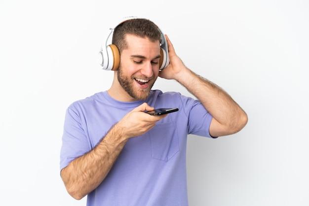 Junger hübscher kaukasischer mann lokalisiert auf weißer hörender musik mit einem handy und gesang