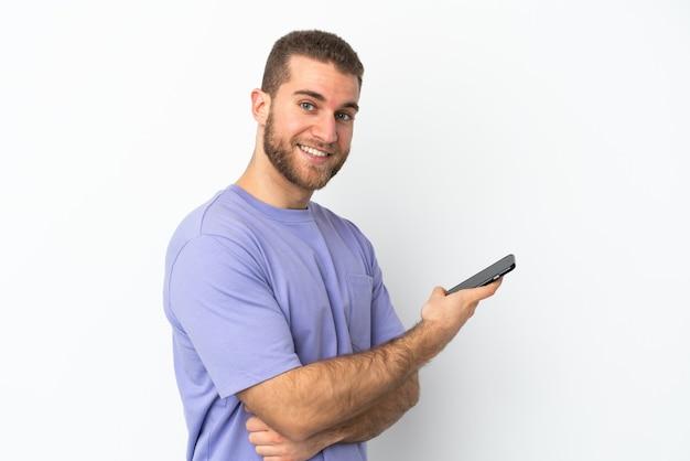 Junger hübscher kaukasischer mann lokalisiert auf weißer wand, die ein mobiltelefon und mit verschränkten armen hält