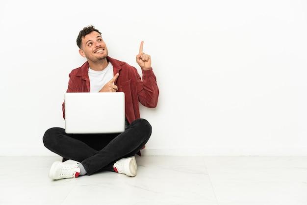 Junger hübscher kaukasischer mann sitzt auf dem boden mit dem laptop, der zeigt