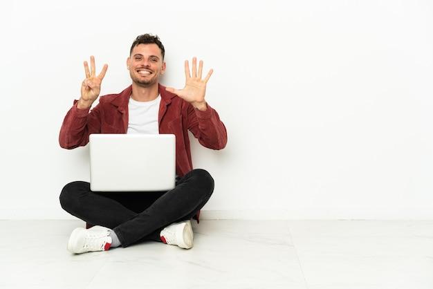 Junger hübscher kaukasischer mann sitzt auf dem boden mit laptop, der acht mit den fingern zählt