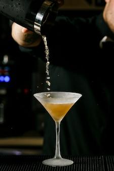 Junger hübscher kellner in mischendem alkoholcocktail der bar. p