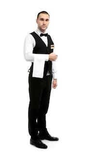 Junger hübscher kellner mit serviette, die auf weiß steht