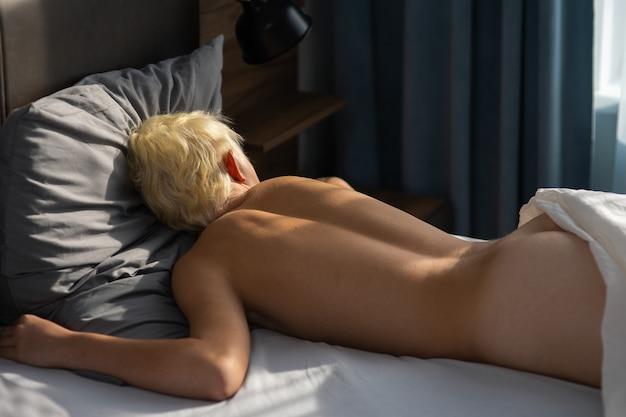 Junger hübscher kerl blond nackt im schlafzimmer mit großen fenstervorhängen und bett