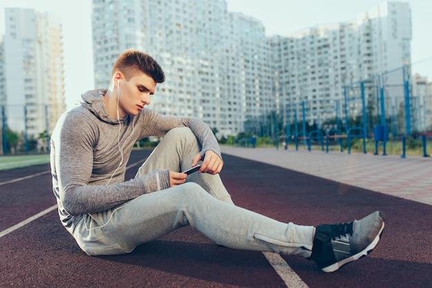 Junger hübscher kerl, der auf laufbahn am morgen auf stadion sitzt. er trägt einen grauen sportanzug. er hört musik und telefoniert.