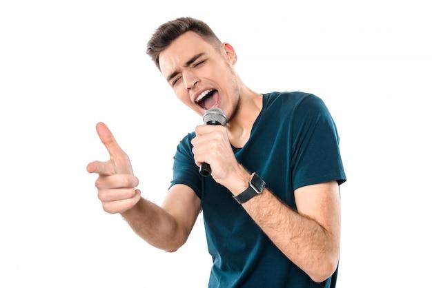 Junger hübscher kerl, der ausdrücklich karaoke singt