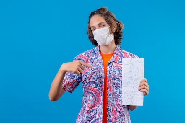 Junger hübscher kerl, der eine gesichtsschutzmaske trägt, die flugtickets hält, die den fünften finger auf sich zeigen, stolzes und selbstbewusstes lächeln, das über blauem hintergrund steht