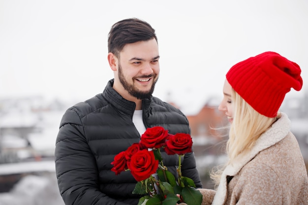 Junger hübscher kerl, der einem mädchen einen strauß rosen am valentinstag gibt