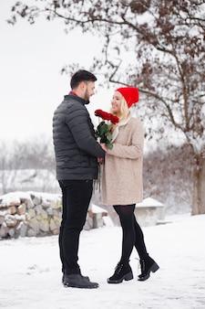 Junger hübscher kerl, der einer frau einen strauß rosen am valentinstag gibt