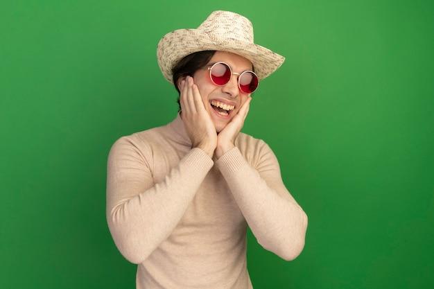 Junger hübscher kerl, der hut mit brille trägt - lokalisiert auf grüner wand