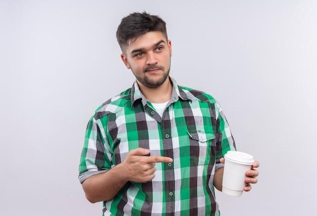 Junger hübscher kerl, der kariertes hemd trägt, das neben dem zeigen auf plastik kaffeetasse steht, die über weißer wand steht