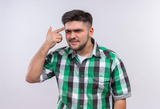 Junger hübscher kerl, der offensiv kariertes hemd trägt und außerdem fragt, ob er über weißer wand stehen soll