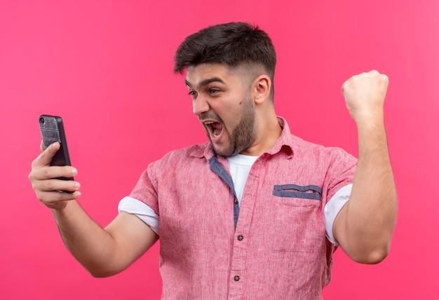 Junger hübscher kerl, der rosa poloshirt hält telefon hält und ja-zeichen mit erhabener faust tut, die über rosa wand steht
