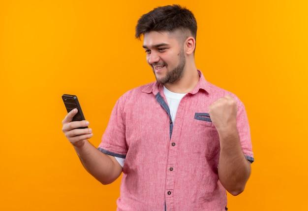 Junger hübscher kerl, der rosa poloshirt trägt, das telefon glücklich tut, tat es mit faust, die über orange wand steht