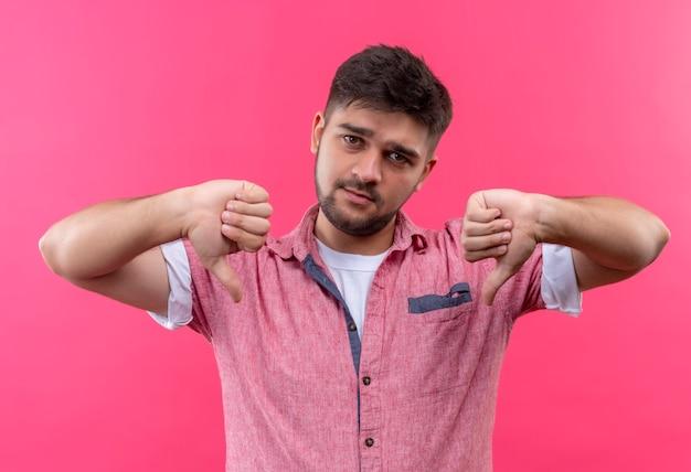 Junger hübscher kerl, der rosa poloshirt trägt, das unglückliche daumen unten tut, die über rosa wand stehen