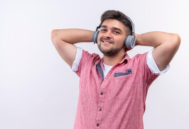 Junger hübscher kerl, der rosa poloshirt und kopfhörer trägt, die musik hören, die glücklich über weißer wand steht