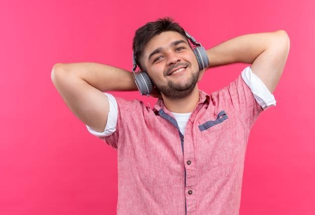 Junger hübscher kerl, der rosa poloshirt und kopfhörer trägt musik genießt, die glücklich über rosa wand steht