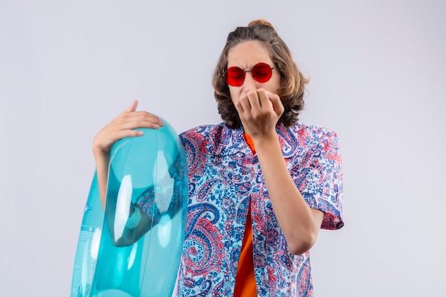 Junger hübscher kerl, der rote sonnenbrille hält, die aufblasbaren ring hält, der gestresste und nervöse beißende nägel sieht, die über weißem hintergrund stehen