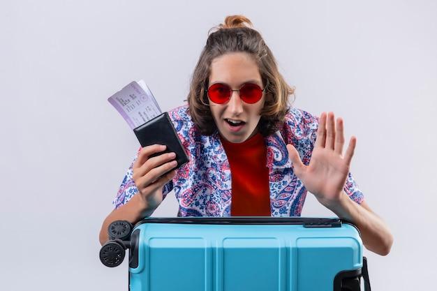 Junger hübscher kerl, der rote sonnenbrille mit reisekoffer hält, der flugtickets hält, die zuversichtlich und glücklich stehen über blauem hintergrund stehen